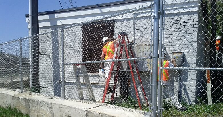 Painters with protective equipment and on ladder